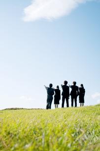 草原に立ち指を指すビジネスマンとビジネスウーマンの後姿の写真素材 [FYI04543754]