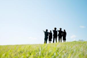 草原に立ち指を指すビジネスマンとビジネスウーマンの後姿の写真素材 [FYI04543755]