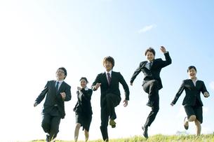 草原を走るビジネスマンとビジネスウーマンの写真素材 [FYI04543756]
