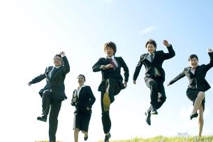 草原でジャンプをするビジネスマンとビジネスウーマンの写真素材 [FYI04543757]