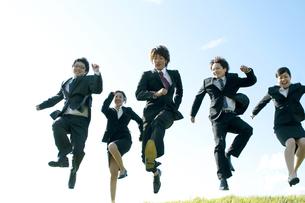 草原でジャンプをするビジネスマンとビジネスウーマンの写真素材 [FYI04543758]