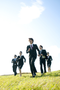 草原を走るビジネスマンとビジネスウーマンの写真素材 [FYI04543759]