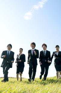 草原を走るビジネスマンとビジネスウーマンの写真素材 [FYI04543760]