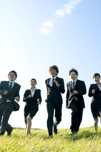 草原を走るビジネスマンとビジネスウーマンの写真素材 [FYI04543761]