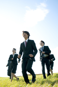 草原を走るビジネスマンとビジネスウーマンの写真素材 [FYI04543762]