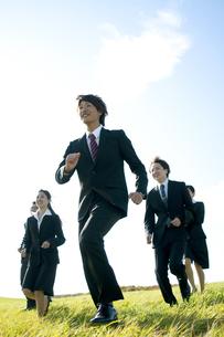草原を走るビジネスマンとビジネスウーマンの写真素材 [FYI04543763]