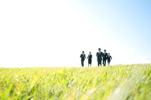草原を走るビジネスマンとビジネスウーマンの写真素材 [FYI04543764]