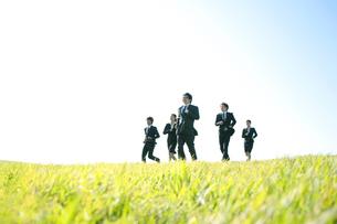 草原を走るビジネスマンとビジネスウーマンの写真素材 [FYI04543766]