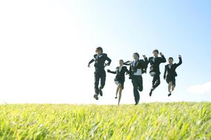 草原でジャンプをするビジネスマンとビジネスウーマンの写真素材 [FYI04543767]