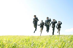 草原でジャンプをするビジネスマンとビジネスウーマンの写真素材 [FYI04543768]