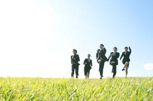草原を走るビジネスマンとビジネスウーマンの写真素材 [FYI04543769]