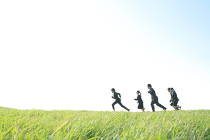草原を走るビジネスマンとビジネスウーマンの写真素材 [FYI04543770]