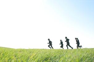 草原を走るビジネスマンとビジネスウーマンの写真素材 [FYI04543772]