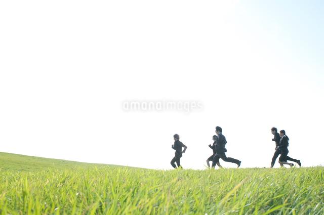 草原を走るビジネスマンとビジネスウーマンの写真素材 [FYI04543773]