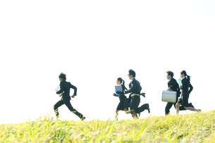 草原を走るビジネスマンとビジネスウーマンの写真素材 [FYI04543774]