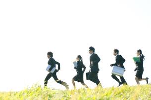 草原を走るビジネスマンとビジネスウーマンの写真素材 [FYI04543775]
