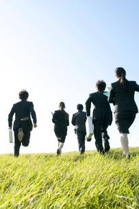 草原を走るビジネスマンとビジネスウーマンの後姿の写真素材 [FYI04543777]