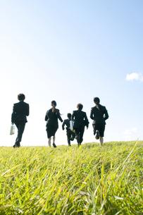 草原を走るビジネスマンとビジネスウーマンの後姿の写真素材 [FYI04543778]