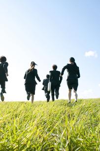 草原を走るビジネスマンとビジネスウーマンの後姿の写真素材 [FYI04543779]