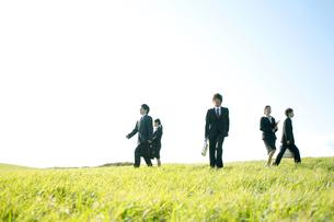 草原を歩くビジネスマンとビジネスウーマンの写真素材 [FYI04543785]