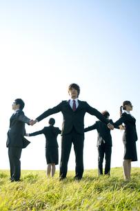 草原で手をつなぎ輪になるビジネスマンとビジネスウーマンの写真素材 [FYI04543790]