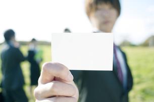 草原で名刺を差し出すビジネスマンの写真素材 [FYI04543795]