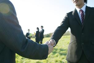 草原で握手をするビジネスマンの写真素材 [FYI04543796]