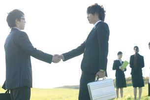 草原で握手をするビジネスマンの写真素材 [FYI04543799]