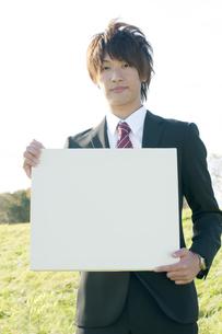 草原でメッセージボードを持つビジネスマンの写真素材 [FYI04543800]