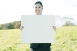 草原でメッセージボードを持つビジネスウーマンの写真素材 [FYI04543803]