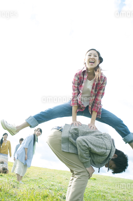 草原で馬跳びをする若者たちの写真素材 [FYI04543823]