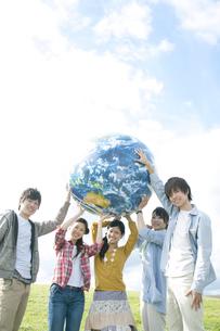 草原で地球のボールを持つ若者たちの写真素材 [FYI04543824]