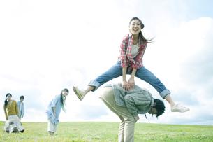 草原で馬跳びをする若者たちの写真素材 [FYI04543828]