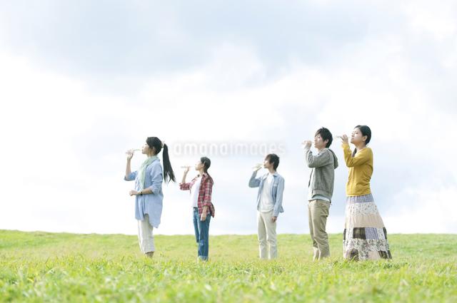 草原で水を飲む若者たちの写真素材 [FYI04543836]
