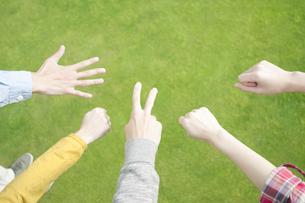 草原でジャンケンをする若者たちの手元の写真素材 [FYI04543860]