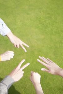 草原でジャンケンをする若者たちの手元の写真素材 [FYI04543861]