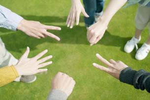 草原でジャンケンをする若者たちの手元の写真素材 [FYI04543862]
