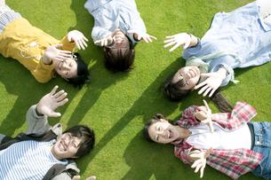 芝生の上に寝転ぶ若者たちの写真素材 [FYI04543873]