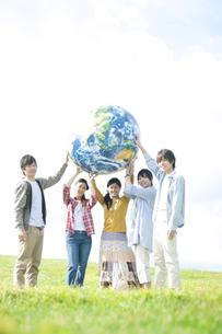 草原で地球のボールを持つ若者たちの写真素材 [FYI04543895]
