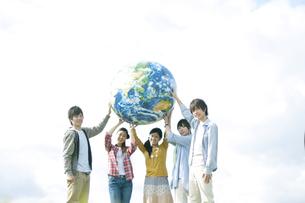 地球のボールを持つ若者たちの写真素材 [FYI04543897]