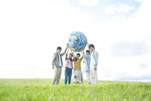 草原で地球のボールを持つ若者たちの写真素材 [FYI04543901]