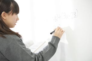 ホワイトボードに数式を書く中学生の写真素材 [FYI04544007]