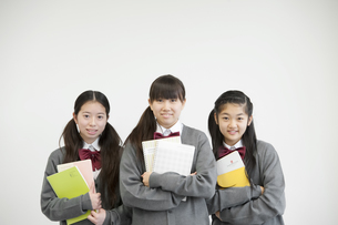 勉強道具を持ち微笑む中学生の写真素材 [FYI04544038]