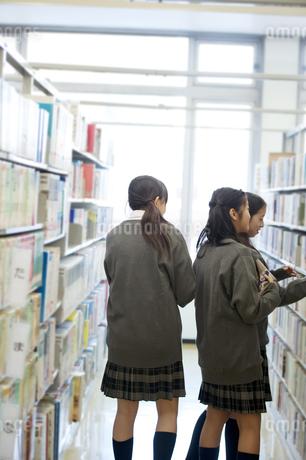 図書館で本を選ぶ中学生の写真素材 [FYI04544048]