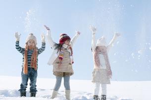 雪を舞い上げる子供たちの写真素材 [FYI04544088]