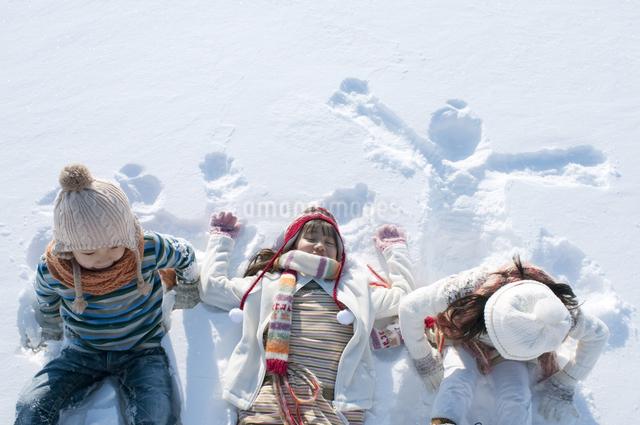 雪原に寝転ぶ子供たちの写真素材 [FYI04544107]