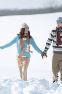 手をつなぎ雪原を歩くカップルの写真素材 [FYI04544117]
