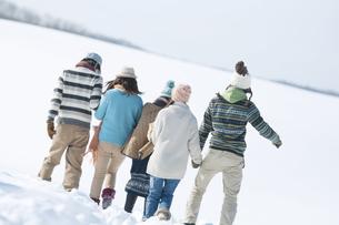 手をつなぎ雪原を歩く若者たちの後姿の写真素材 [FYI04544124]