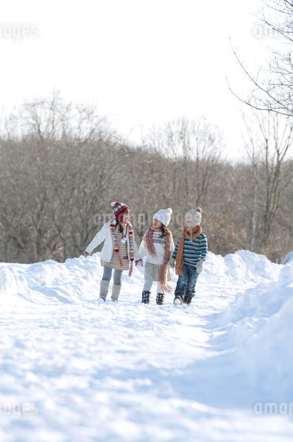 雪道を歩く子供たちの写真素材 [FYI04544225]