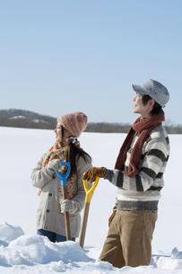 雪原でスコップを持ち微笑むカップルの写真素材 [FYI04544267]